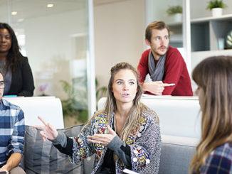 personer som sitter runt ett bord i kontorsmiljö