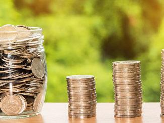 staplar av mynt bredvid en glasburk fylld med mynt